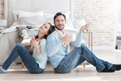 Happy dreamy couple sitting on the floor Stock Photos