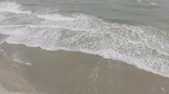 Aerial view of waves crashing onto beach Stock Footage