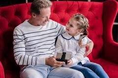 Amused girl with her grandfather holding the game console Stock Photos