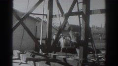 1937: men erect steel girders and beams atop tower next to completed structure Stock Footage