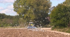 Farmer plows arable field in clay area - tractor rides away from camera Stock Footage