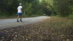 Elderly athlete runner running on road in autumn forest Stock Footage
