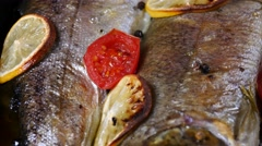 Delicious trout fish baked with lemon, tomatoes and spices Stock Footage