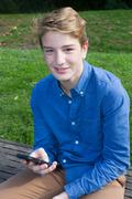 Young handsome happy modern teen talking texting on phone Stock Photos