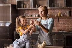 Amused little girl mixing the pastry with her mother Stock Photos