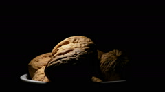 Walnuts nut fruit in a white bowl gyrating on black background Stock Footage