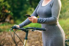 Female cyclist using mobile phone application Stock Photos