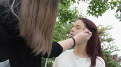 Beautiful teen with her makeup artist apply makeup, outdoor scene Stock Footage
