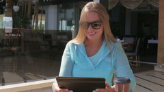Pretty woman use a tablet computer drink coffee sitting in a cafe in the summer Stock Footage