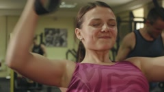 Athlete girl performs exercises with a T-Rex at hard training in the gym close Stock Footage