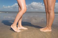 Beautiful woman legs, walking on the beach Stock Photos