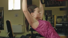 Young athlete girl performs exercises with a T-Rex at hard training in the gym Stock Footage