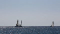 Sailboats glide across the sparkling surface of the sea Stock Footage