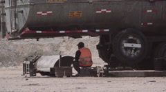 Worker resting under fuel truck Stock Footage