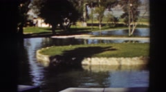 1937: a well maintained pond with rock-lined banks sits in a grassy area Stock Footage