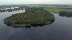 Approaching natural green island in the lake. Aerial view Stock Footage