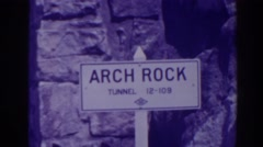 "1938: sign indicating ""arch rock tunnel,"" river below and cars traveling through Stock Footage"