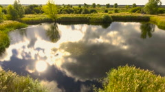 Natural pond reflecting sun and sky of water surface. Aerial view Stock Footage
