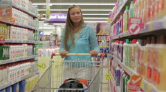 Happy woman selects household chemicals in the supermarket Stock Footage
