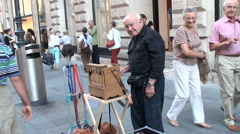 The people thanking an elderly man who plays the music with a street organ Stock Footage