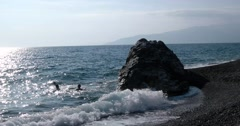 View of Waves Rolled at Sea Coast Line With Huge Rock With People Swiming Stock Footage