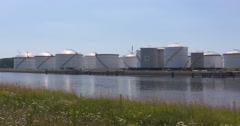 Crude oil storage tanks alongside canal in Seaport Rotterdam Stock Footage