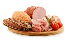 Assorted meat products including ham and sausages isolated on white. Stock Photos
