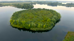 Natural lake island covered in trees and bush, misty morning, aerial view Stock Footage