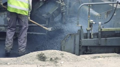 Asphalt machine lays asphalt. Road worker lays asphalt shovel Stock Footage