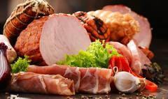 Assorted meat products including ham and sausages. Stock Photos