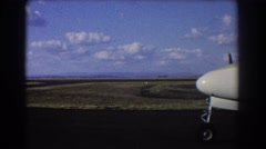 1967: nose of airplane and front wheel extend over paved runway by field Stock Footage