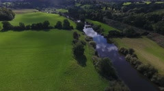 Tilting aerial view of a river that runs through beautiful countryside. Stock Footage