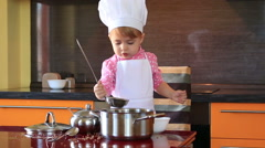 Little cute girl in chef suit playing in the kitchen with a ladle and saucepan Stock Footage
