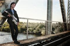 Scratch effect on photo men with guitar on a railroad Stock Photos
