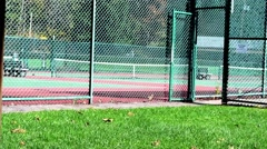 Medium shot of tennis court entrace in park in autumn Stock Footage