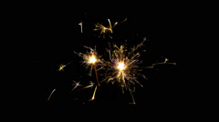 Two sparklers, burning from top to bottom, on black blackground. Stock Footage
