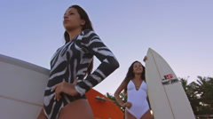 Two Fashion Surf Lifestyle Girls Standing Up Holding Surfboards At The Beach Stock Footage