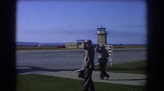 1967: two men walk towards an airplane on a runway at the airport PERTH Stock Footage