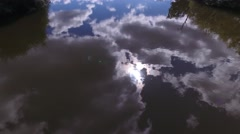 Low aerial view flying over a river with reflections of the sun and clouds. Stock Footage