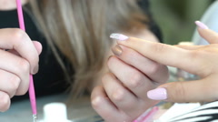 Nails with manicure covered with nail polish on colored pearls Stock Footage