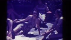 1937: people in bathing suits lounge outdoors in the sunshine while enjoying Stock Footage