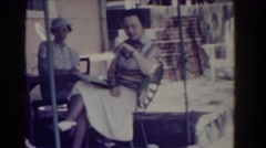 1937: ladies posing for video outside by tables and one gets startled Stock Footage