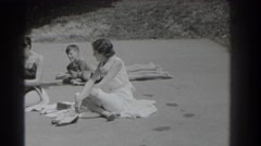 1937: group of people sitting on the ground outside in their bathing suits Stock Footage