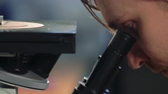 Scientist looking through a microscope in a laboratory. Young doctror diagnostic Stock Footage