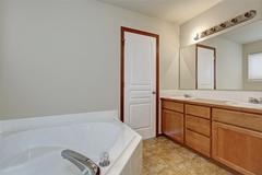White bathroom interior with corner bathtub and vanity cabinet with two sinks Stock Photos