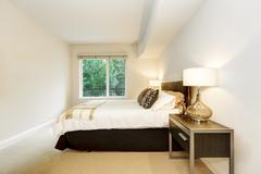 Neat bedroom with a bed and nightstands with lamps. Carpet floor and white wa Stock Photos