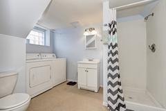 Light blue bathroom interior with laundry appliances. Northwest, USA Stock Photos