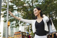 Attractive Happy Woman with Bag Hailing a Cab Stock Photos