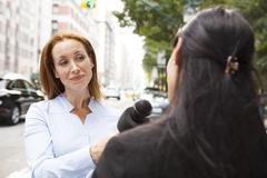 Reporter with a Microphone Interviews Woman Stock Photos