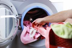 Put cloth in washer Stock Photos